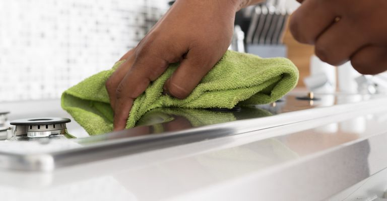 person cleaning stove burners in kitchen with green towel