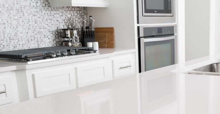 Clean kitchen with white cabinets and counter tops, stove and knife sets with cutting boards