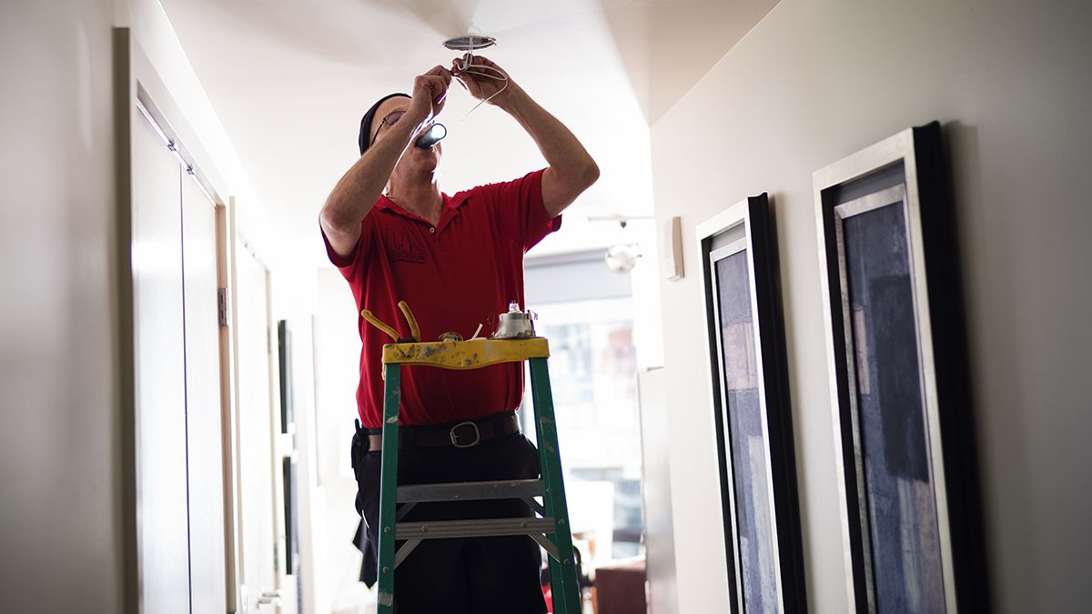 handyman standing on ladder fixing light fixture on ceiling in a hallway
