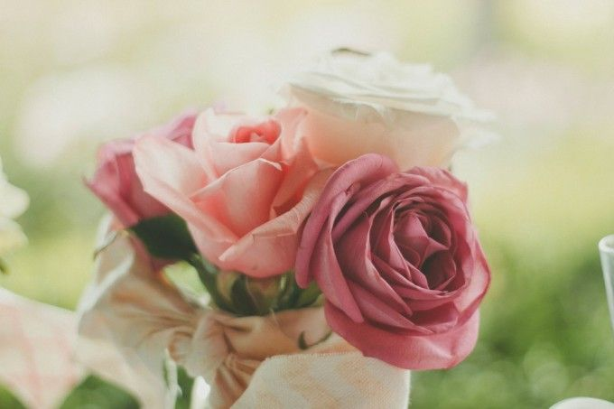 wedding bouquet of roses - pink, white, and fuchsia colored tied with a cream bow.
